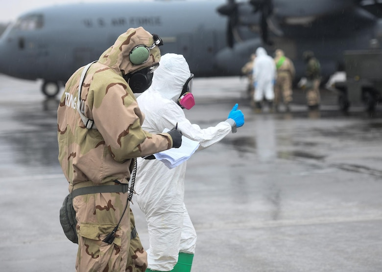 Two Airmen walk towards a large grey plane in protective clothing.