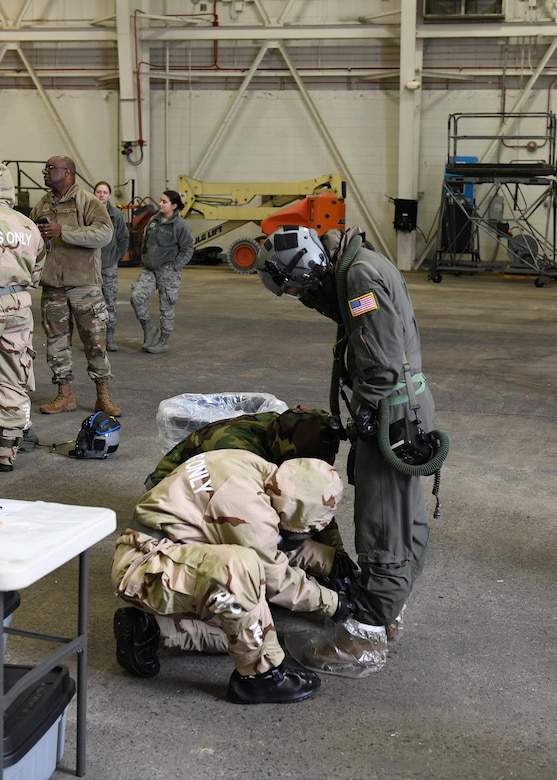 Two Airmen untie another Airman's boots.