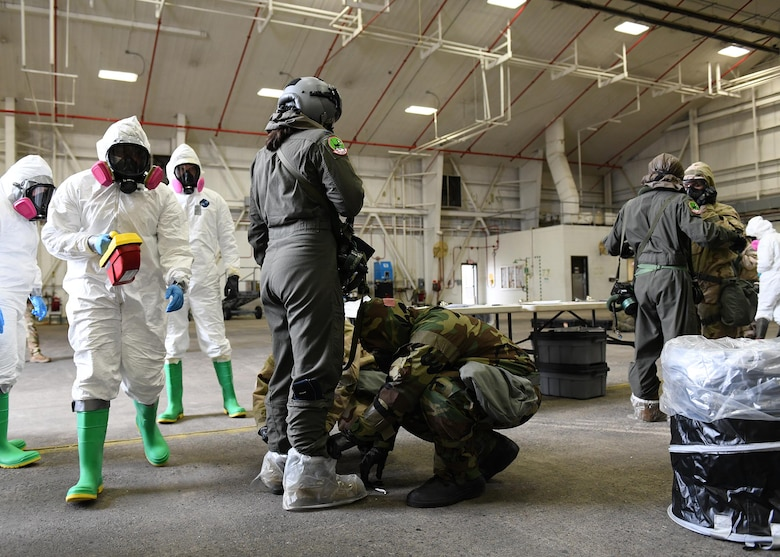 Multiple Airmen check another Airmen for simulated radiation with equipment.