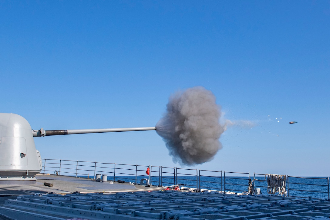 A plume of smoke and a missile are seen as a gun fires from a ship.