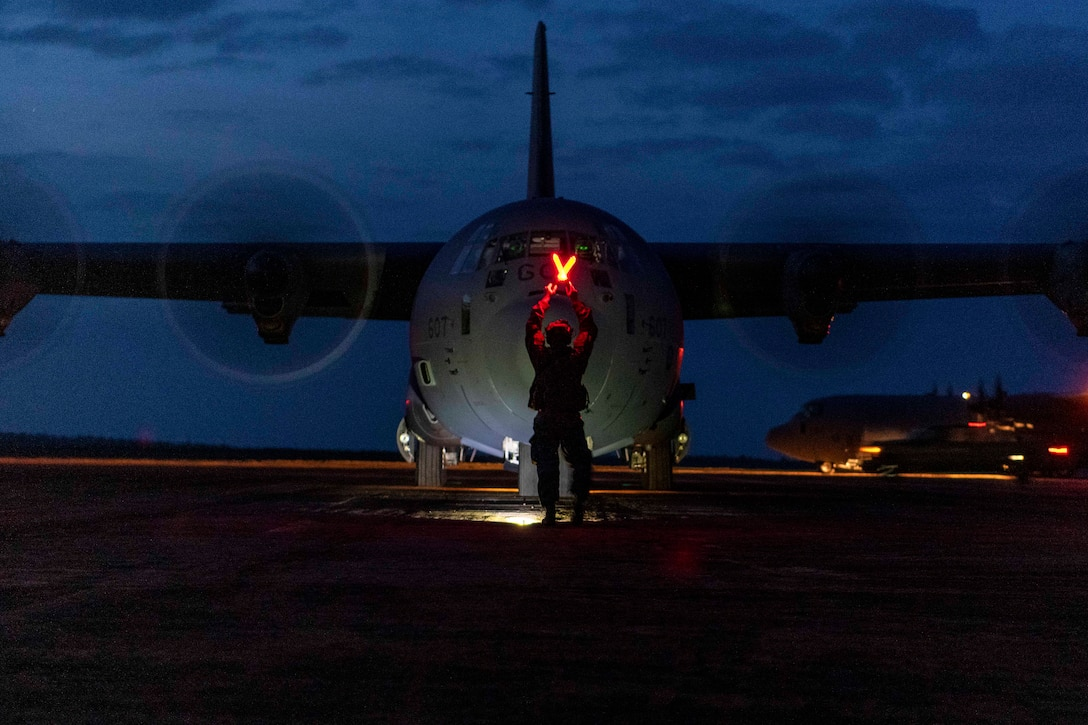 An airman provides signals in front of an aircraft.