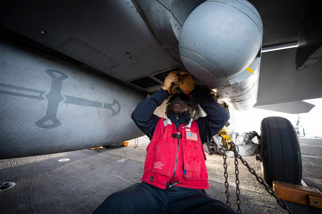 A sailor works on the underside of an aircraft.