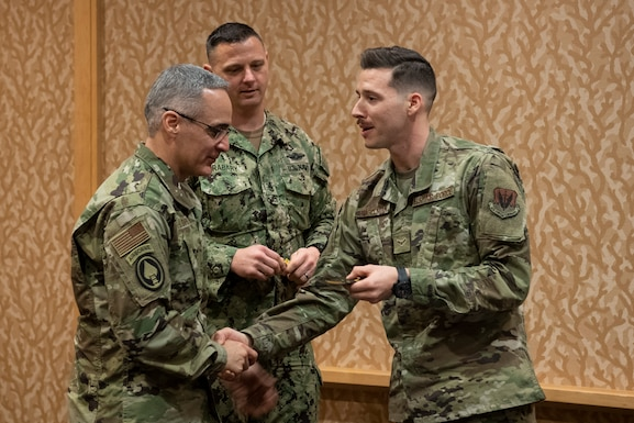 """U.S. Air Force Airman 1st Class Jonathan Engelman, an electronic integrated systems mechanic with the California Air National Guard's 144th Fighter Wing, right, gives his squadron patch to Senior Enlisted Advisor to the Chairman of the Joint Chiefs of Staff Ramón """"CZ"""" Colón-López, left, during the California Military Department's annual leadership conference, Jan. 18, 2020, in San Diego."""