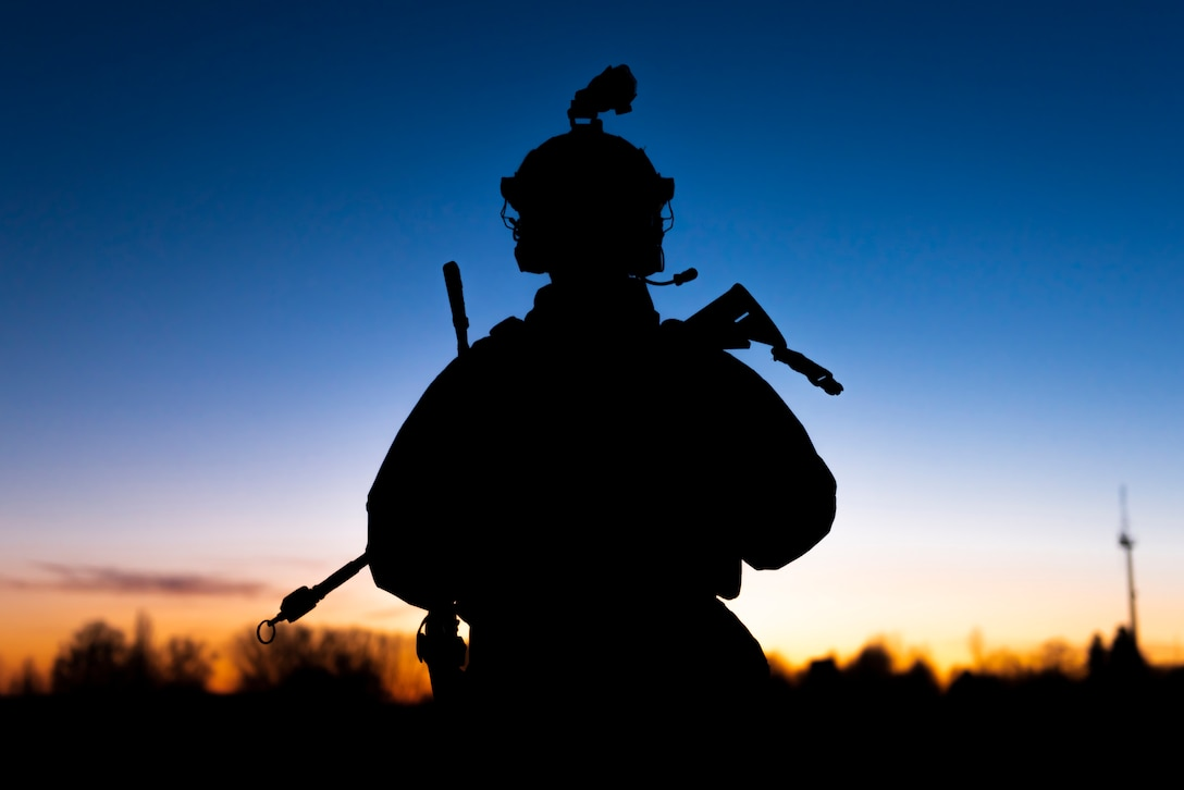 An airman  holding a weapon  is seen in silhouette at sunset.