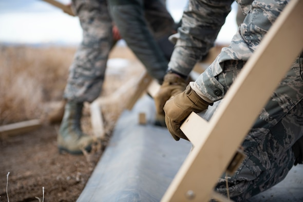 Airman from the 366th Civil Engineer Squadron use teamwork to construct a tactical shelter during the Base Emergency Engineer Force training, Jan. 23, 2020, at Mountain Home Air Force Base, Idaho. This training was conducted to equip Airman with skills from other career fields to enhance their readiness. (U.S. Air Force photo by Senior Airman Tyrell Hall