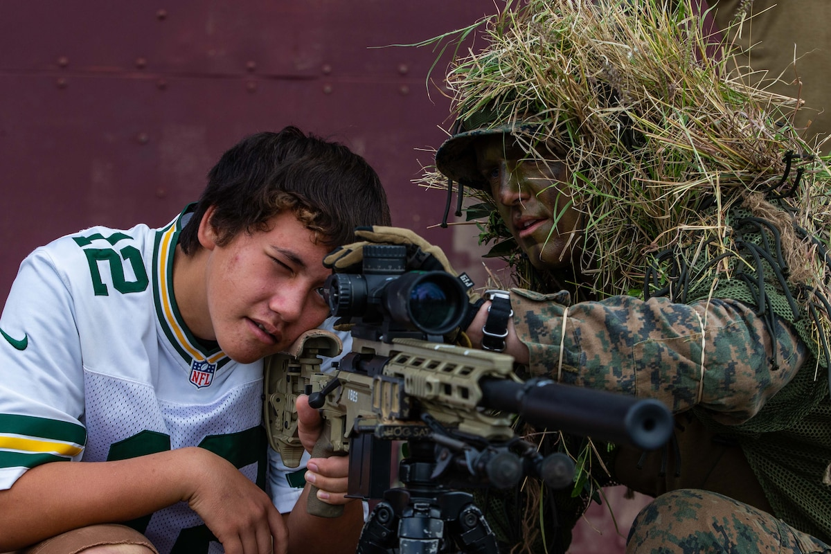 A boy looks through the scope of a weapon held by a Marine.
