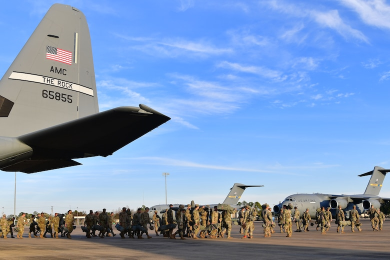 Soldiers from the 4th Brigade Combat Team (Airborne), 25th Infantry Division, at Joint Base Elmendorf-Richardson, Alaska, perform gear checks prior to boarding a C-130J Super Hercules during the joint forcible entry and airborne assault.