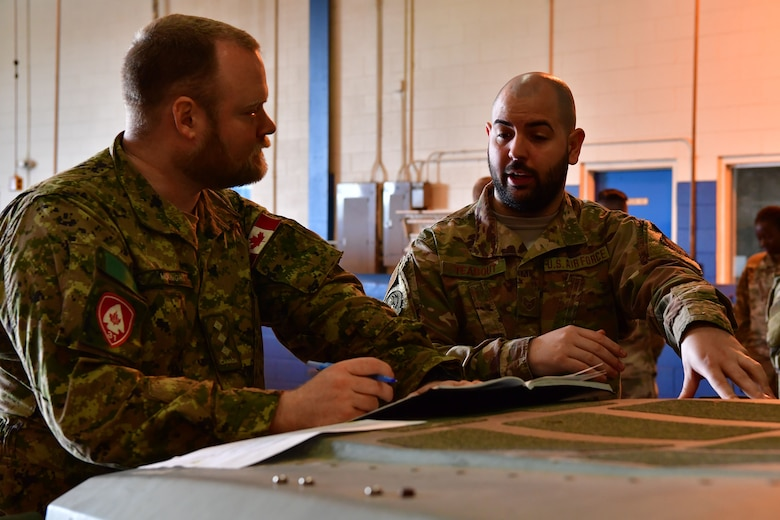 An Airman from the 621st Contingency Response Wing speaks with a member of the 31st Canadian Brigade Group before the joint forcible entry and airborne assault, which kicked off Green Flag Little Rock 20-03.