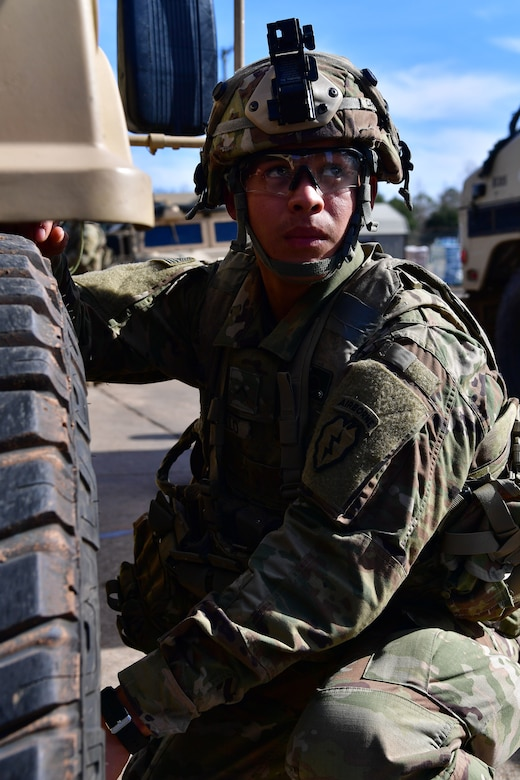 A soldier from the 4th Brigade Combat Team (Airborne), 25th Infantry Division, at Joint Base Elmendorf-Richardson, Alaska, checks the tire pressure on a Humvee during Green Flag Little Rock 20-03.