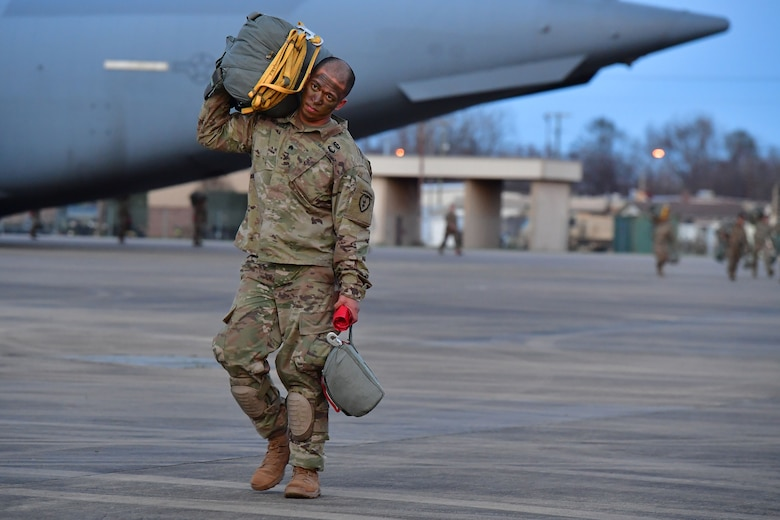 A soldier from the 4th Brigade Combat Team (Airborne), 25th Infantry Division, at Joint Base Elmendorf-Richardson, Alaska, walks to a C-17 Globemaster III during the joint forcible entry and airborne assault which kicked off Green Flag Little Rock 20-03.