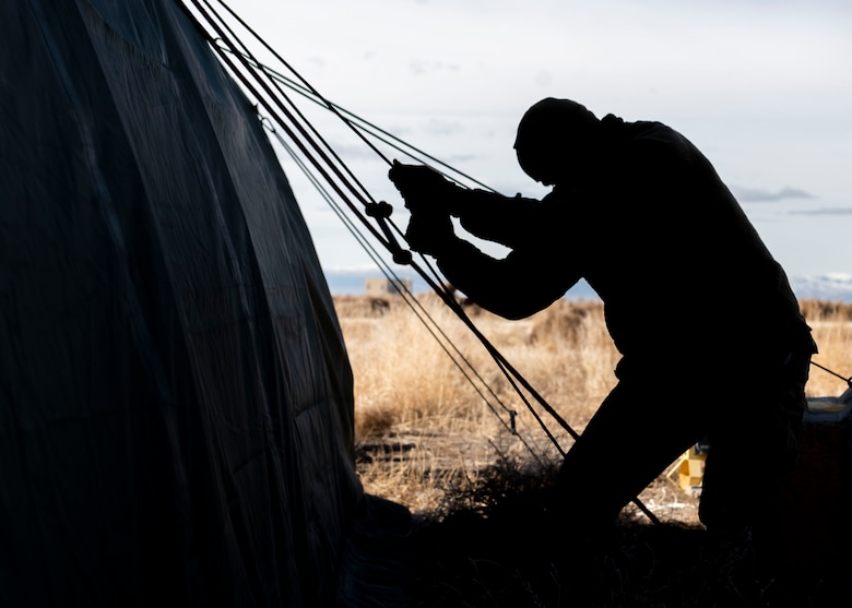 An Airman from the Civil Engineer Squadron hoists a tent grounding line during the Base Emergency Engineer Force training, Jan. 23, 2020, at Mountain Home Air Force Base, Idaho. This training was conducted to equip Airman with skills from other career fields to enhance their readiness. (U.S. Air Force photo by Senior Airman Tyrell Hall)