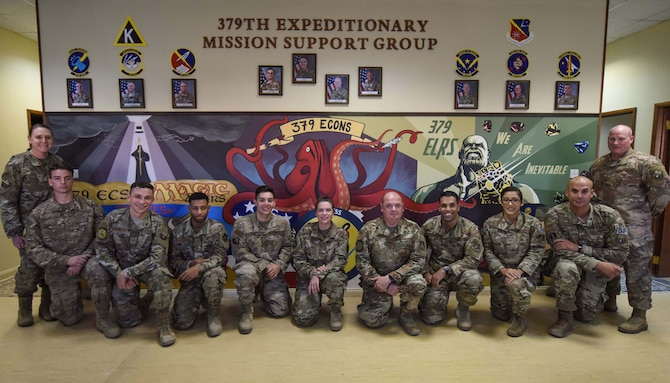 379th Expeditionary Mission Support Group leadership stands alongside mural artists at Al Udeid Air Base, Qatar on Dec. 5, 2019. The mural took 250 hours of volunteering to be completed and many of the Airmen did not know each other prior to creating the artwork. (U.S. Air Force photo by Senior Airman Shay Stuart)