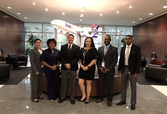 Three women and three men stand in front of a Fedex model plane.