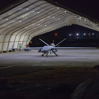 A U.S. Air Force MQ-9 Reaper remotely piloted aircraft equipped with external fuel tanks and armed with munitions sits in a hanger prior to Intelligence, Surveillance, and Reconnaissance operations at Ali Al Salem Air Base, Kuwait, July 23, 2019. (Tech. Sgt. Michael Mason)