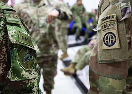 A U.S. Army 82nd Airborne Division and Colombian Army 2nd Special Forces Battalion Paratrooper stand next to each other.