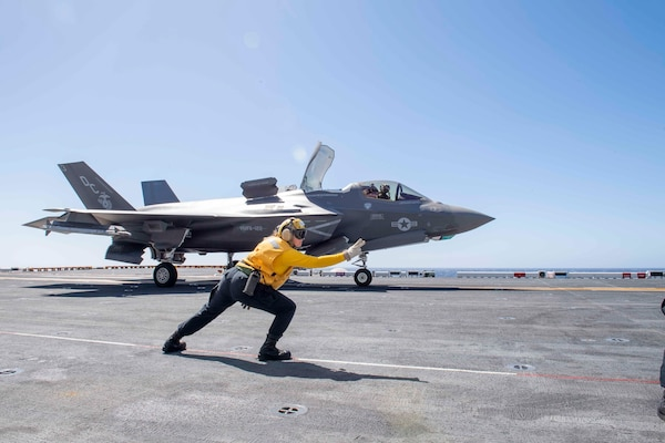 Person signals for a fighter jet to take off the runway of a ship.