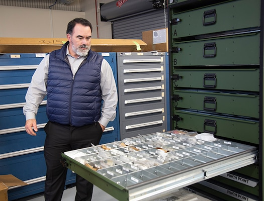 DLA Aviation customer account specialist looks into a container system drawer at a Black Hawk maintenance inspection kit
