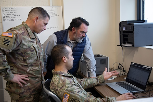 DLA Aviation team members review computer reports with Army service member.
