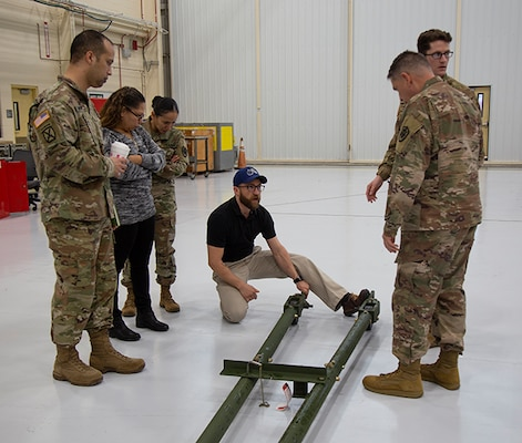 Maintenance chief talks about aircraft tow bar with DLA Aviation team members.