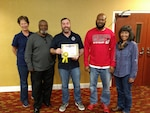 Warehouse Supervisor Willie Anderson (left center), Area Manager Mike Kelly (center) and Operations Supervisor Willie Mitchell (right center) accept the first place site award from South-East Deputy Director Audrey Weber (far left) and South-East Director Kathy Atkins-Nuñez (far right).