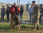 Staff Sgt. Matthew Erfman, 802nd Security Forces Squadron military working dog handler (left) and Staff Sgt. Sean Tucker, 802nd Security Forces Squadron military working dog handler (right) conduct a demonstration with military working dog Tarzan before a group of area school superintendents and administrators at Joint Base San Antonio-Lackland Annex Jan. 23. The group of 15 school superintendents and administrators toured JBSA-Lackland at the invitation of JBSA leaders.