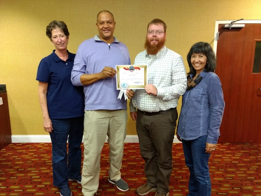 — Area Manager Kevin Vaughn (left center) and Warehouse Supervisor Lucas Grant (right center accept the second place site award from South-East Deputy Director Audrey Weber (far left) and South-East Director Kathy Atkins-Nuñez (far right).