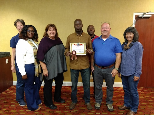 South-East Deputy Director Audrey Weber (far left) helps present the third place award to (from left to right) Centralized Demil Division Warehouse Supervisor La Toya Smith, CDD Operations Supervisor Gail Haas-Sibley, Area Manager Reggie McFadden, CDD Warehouse Supervisor Nathaniel Smith and Site Supervisor Alan Wilkey along with South-East Director Kathy Atkins-Nuñez (far right).