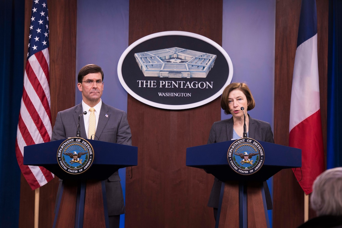 Two people stand at podiums in front of a Pentagon sign and an American flag and a French flag.