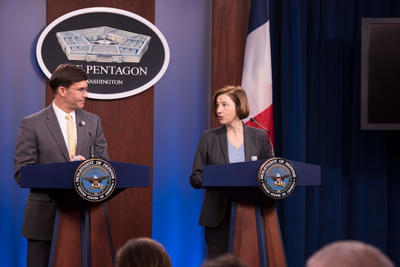 Two people stand at podiums in front of a Pentagon sign.