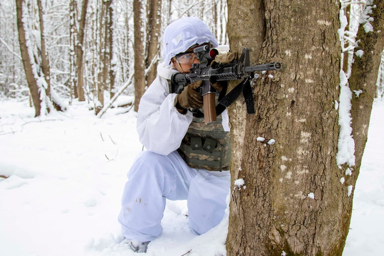 A soldier points a weapon while standing in snow.