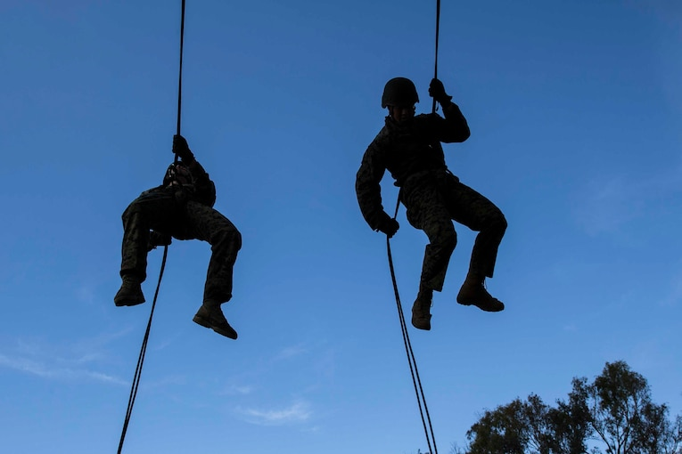 Marines rappel down a rope.