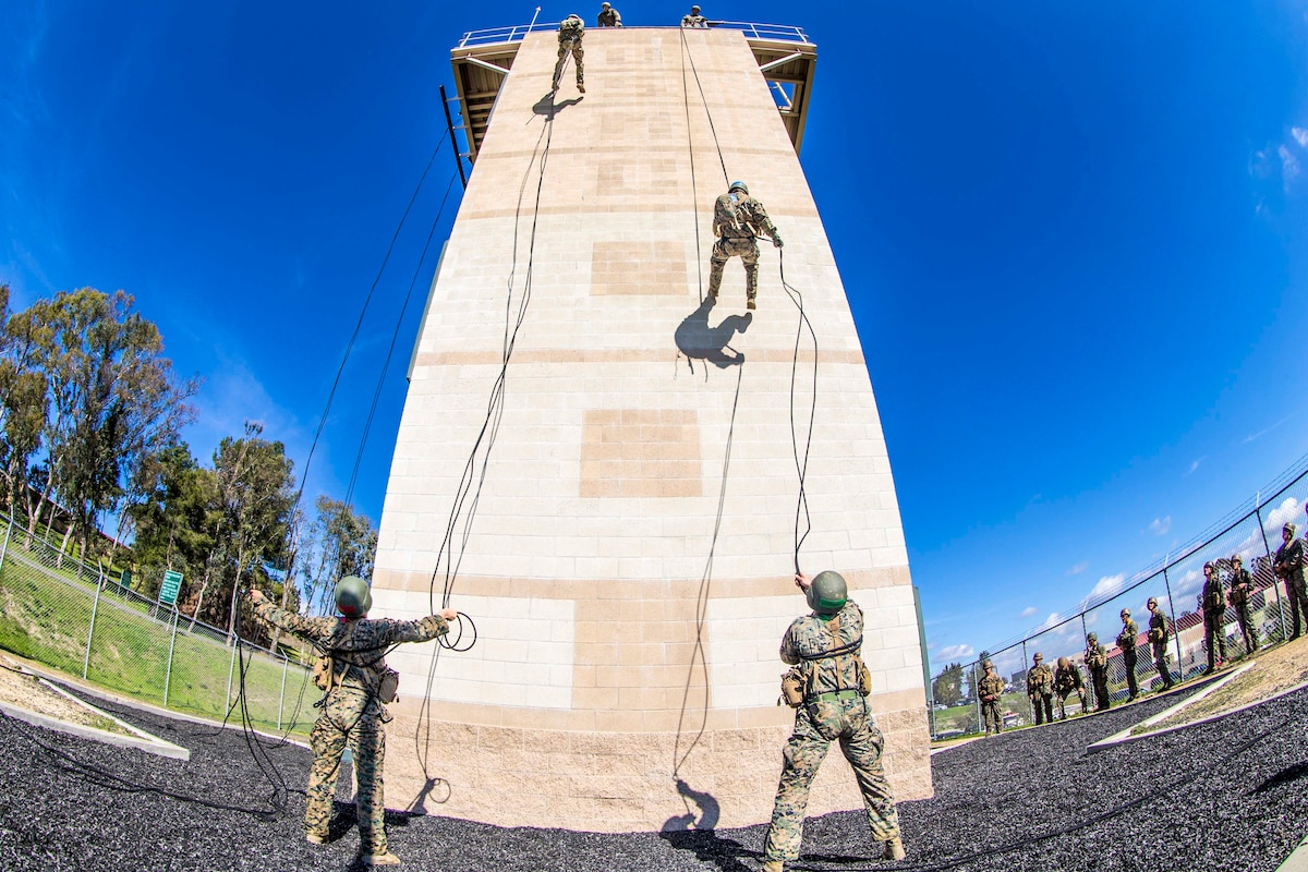 Marines rappel down the side of a wall.