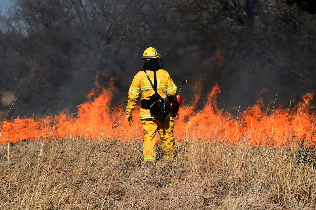Lt. Michael Beane, with the Tinker Fire Department, carefully watches the flames in a prescribed burn close to base housing, lodging and the Tinker Club Mar. 6. Natural Resources and Tinker Fire Department personnel assisted a team from the Air Force Wildland Fire Branch in the prescribed burn. The burns eliminate invasive and non-native grasses and plants and act as a fertilizer, allowing new, productive growth in the Tinker grassland areas.