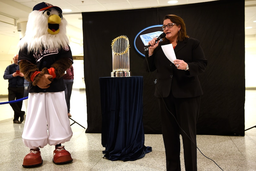 A woman holding a microphone stands in front of a trophy. Nearby is a person in a large bird costume.
