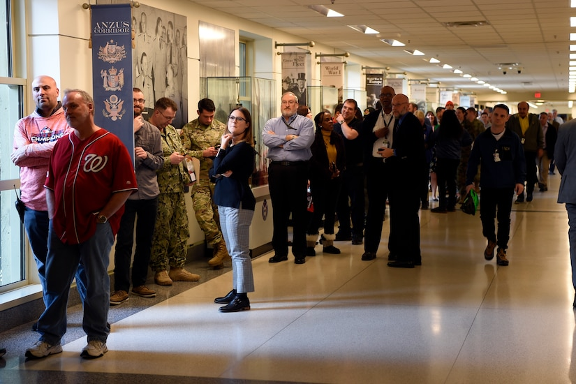 Civilians and military personnel line up in a hallway in the Pentagon.
