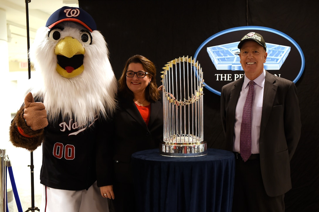 A person in a large bird costume, a woman and man stand behind a trophy, which is situated on a small table.
