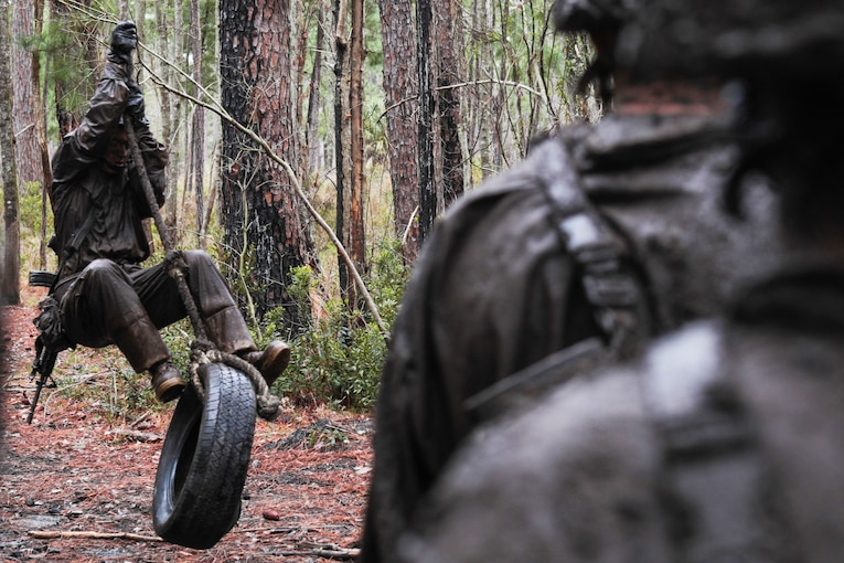 A Marine recruit stands on a tire swing as other recruits watch.