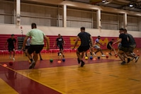 U.S. Marines participating in a dodgeball holiday tournament sprint towards the dodgeballs, Marine Corps Base Hawaii (MCBH), Dec. 23, 2019. The event was hosted by the Single Marine Program and highlighted the support vendors on base have for the troops. (U.S. Marine Corps photo by Lance Cpl. Jose Angeles)