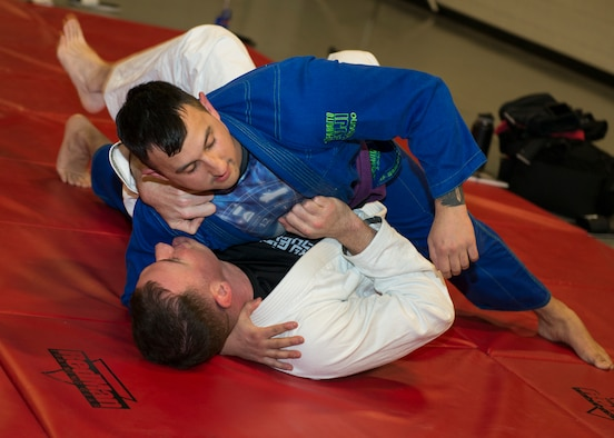 U.S. Air Force Master Sgt. Ian McMahon (top), combatives instructor and Security Forces Squadron flight chief, 103rd Airlift Wing, Connecticut Air National Guard, grapples with Tech. Sgt. Brian Davies, 103rd Security Forces defender, during an informal jiu-jitsu session at Bradley Air National Guard Base, East Granby, Conn. Jan. 23, 2020. The group that practices jiu-jitsu at the 103rd AW monthly to build camaraderie between the members while utilizing combatives skills and outside experience in the martial art. (U.S. Air National Guard photo by Staff Sgt. Steven Tucker)