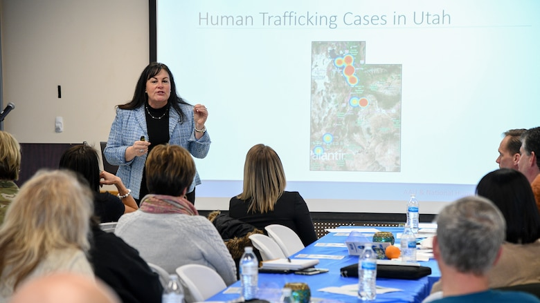 Allison Smith, education and outreach specialist for the Trafficking in Persons Program with the Refugee and Immigrant Center in Salt Lake City, stands in front of a screen depicting human trafficking hot spots across the state of Utah. Audience members look on in the foreground.