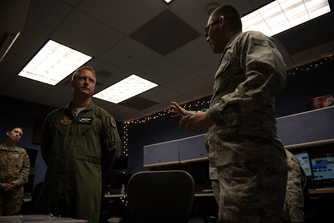 U.S. Air Force Senior Airman Alan Garcia, 325th Fighter Wing Tyndall Command Center junior emergency actions controller, right, briefs U.S. Air Force Col. Brain Laidlaw, 325th Fighter Wing commander, left, at Tyndall Air Force Base, Florida, Jan. 24, 2020. Garcia arrived on station in May 2019 and has provided ideas for improvement and was instrumental in unit training.   (U.S. Air Force photo by Staff Sgt. Magen M. Reeves)
