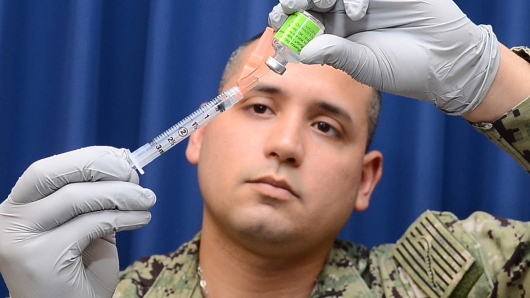 A man wearing gloves prepares a syringe with the influenza vaccine
