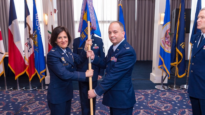 Two people, a woman on the left and a man on the right, in dark blue Air Force service dress uniforms are both holding a guidon flag. Another man in the dark blue Air Force service dress uniform is standing at the position of attention on the right side of the picture. There are numerous, multicolored flags in the background.