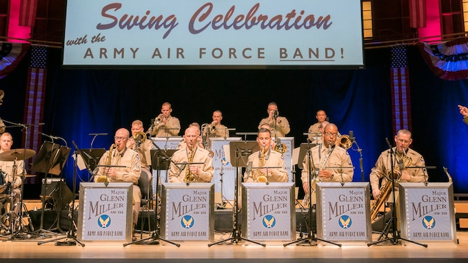About 15 instrumentalist are sitting and performing while dressed in the light brown uniforms that look like what was worn during Army Air Force days. Above them on the large screen are the words: Swing Celebration, with the Army Air Force Band. There are five signs in front of the front row of musicians that read: Major Glenn Miller and his Army Air Force Band.