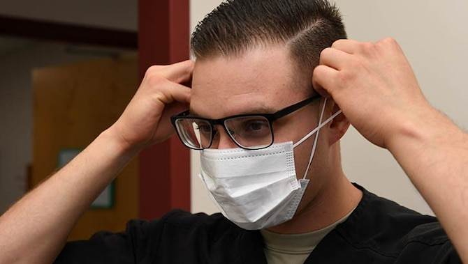 A dental assistant with the 319th Medical Group, demonstrates proper sanitary procedure by putting on a face mask at the medical treatment facility at Grand Forks Air Force Base, North Dakota.