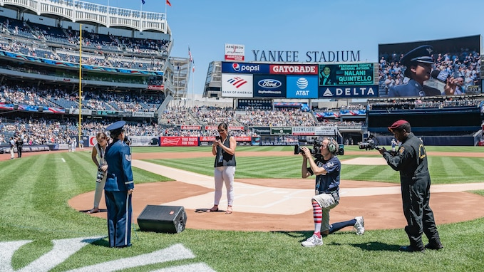 "Woman in dark blue Air Force ceremonial uniform singing the national anthem from behind home plate in Yankee Stadium. Four people are standing and kneeling a few feet in front of her with cameras in their hands, and the words ""Yankee Stadium"" is visible in the distance with several multicolored advertisements below, and a large screen can be seen projecting the image of the vocalists face."