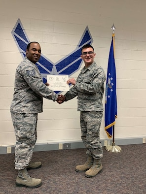 Airman Joshua Olesen, 365th Training Squadron instrument flight control systems apprentice course graduate, left, receives his completion of training certificate at Sheppard Air Force Base, Texas. (Courtesy photo)