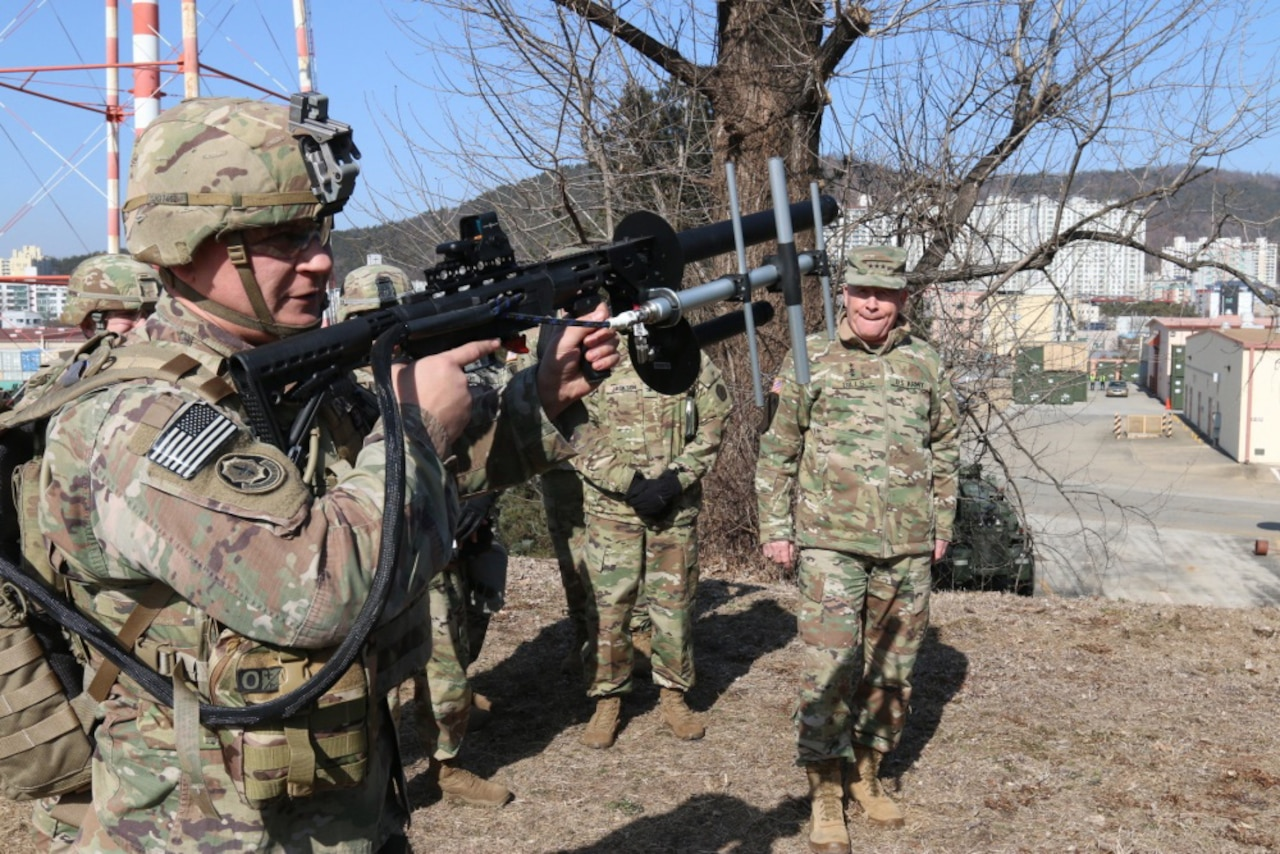 Men in military uniforms stand outside watching a soldier holding a rifle.