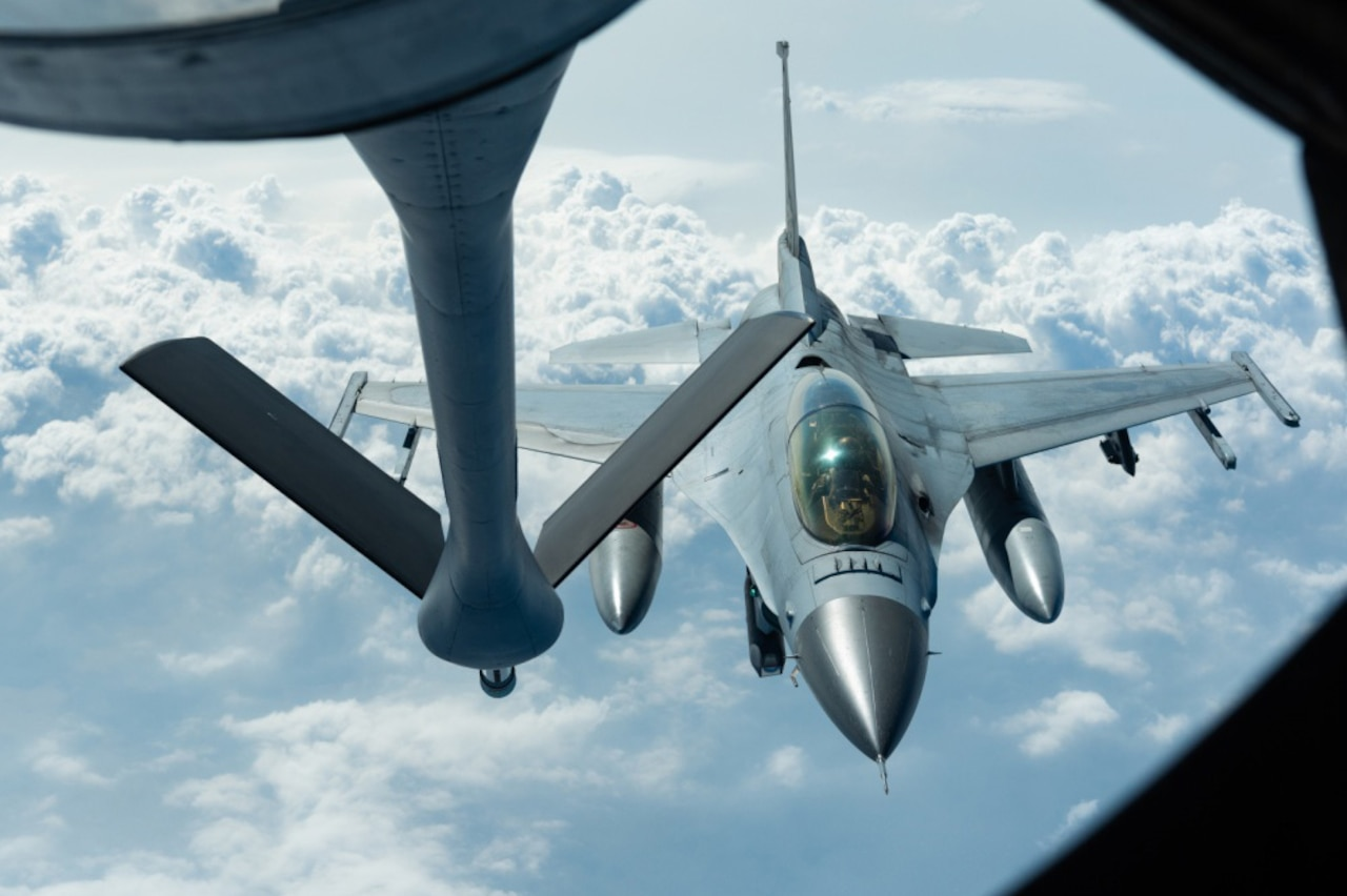 Fighter jet approaches tanker aircraft for aerial refueling.