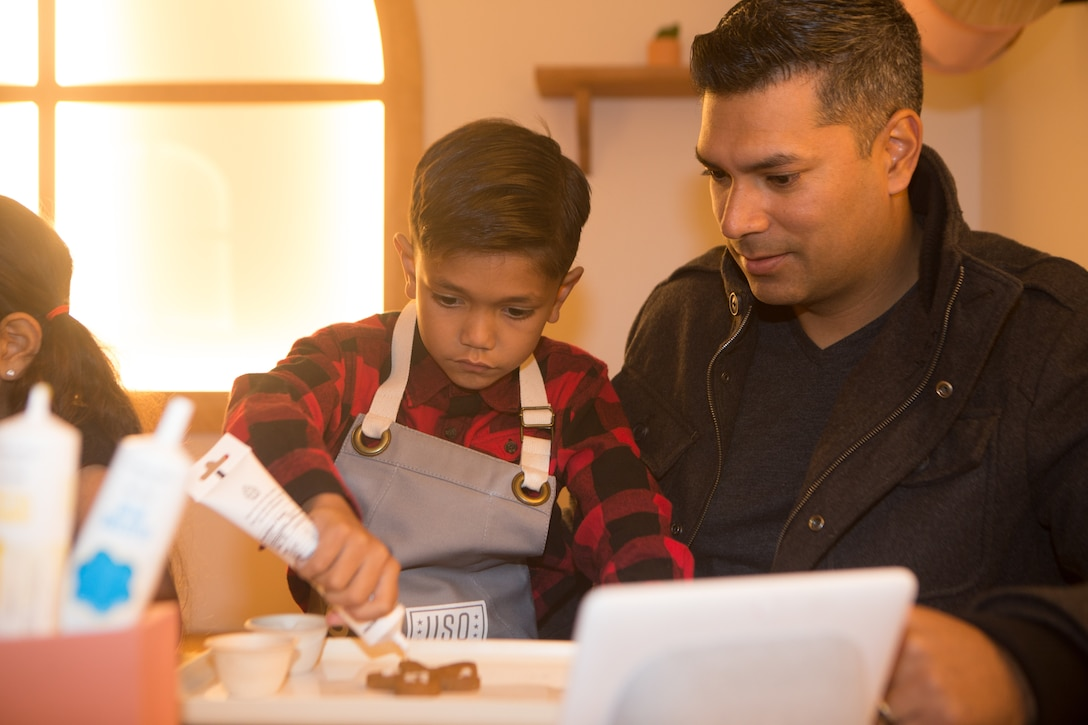Man watches his son decorate with icing